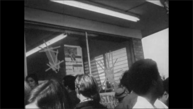 1970s: Men stand on building roof. Rioters and protestors carry banners in street.  Protestors gather outside military base.