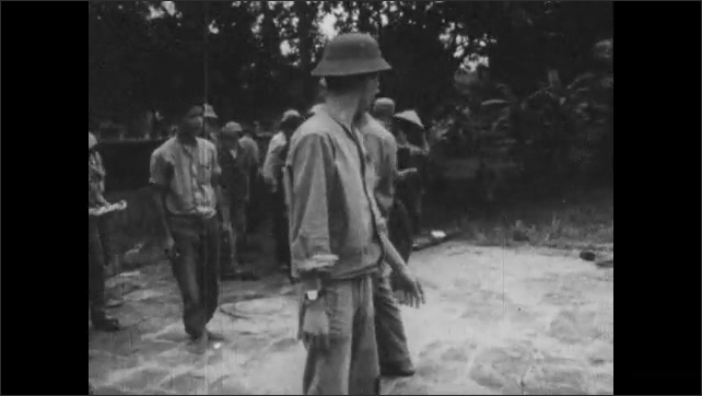 VIETNAM 1960s: Airplane target is positioned for Vietnamese soldiers to practice shooting while being trained. People stand up from ground and get in formation.