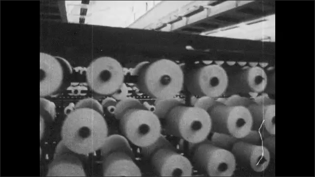 VIETNAM 1960s: Sign on wall in factory. Wheels on conveyor belt. Machines at work. Women at work on machines.