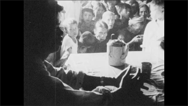 Vietnam 1960s: Woman sings.  People sit and listen.  Men stand.  Sewing machine.  Man gestures.