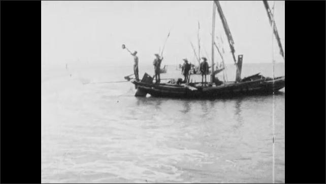 Vietnam 1960s: Soldiers aim guns.  People repair nets.  Men on boats.