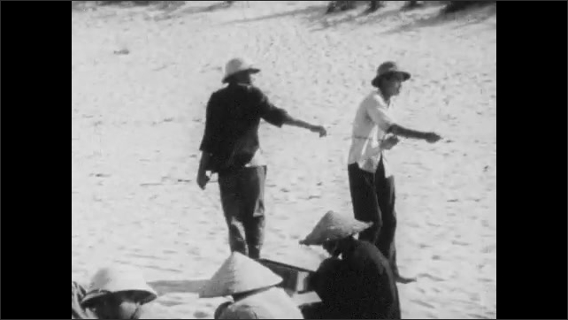 Vietnam 1960s: Boat.  Man unties sails.  Nets on beach.  People work.
