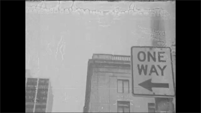 1960s: Large estate. Policeman. Buildings, street sign, large mansion. Police surround African American man.