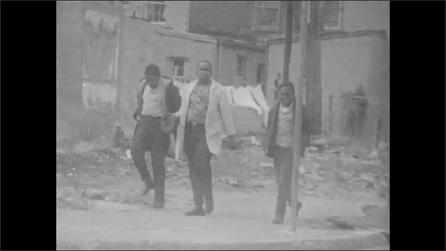 1960s: Man runs across empty lot. Three boys walk through urban neighborhood. Man talks.