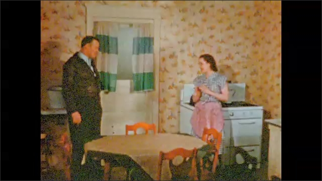 1950s: UNITED STATES: lady and man talk inside kitchen. Lady stands by cooker.