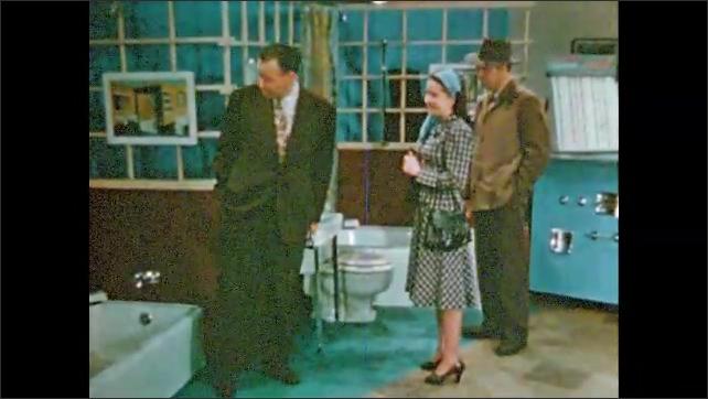 1950s: Man shows couple bathroom fixtures. Woman talks.