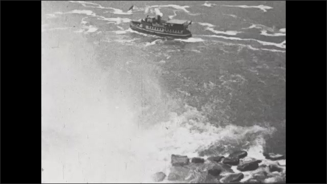 1930s: People standing on rocks at base of waterfalls as steamboat goes by. Title card.