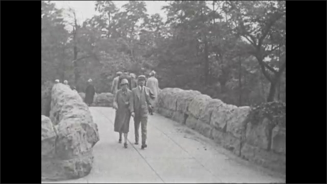 1930s: Sign for Three Sister Islands. People walking over bridge at park.