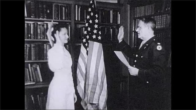 """1930s: Text reads """"In the Service of their country.""""  Woman takes oath.  Man and woman speak."""