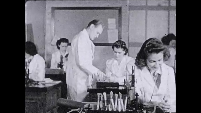 """1930s: Women work in lab.  Man stands and talks.  Text reads """"The study of normal anatomy and physiology helps her to understand the deviations which occur in the sick."""""""