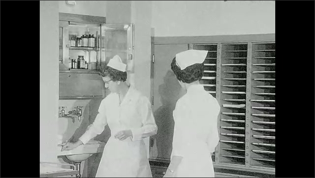 1960s: Hospital.  Women talk at nurses station.  Woman puts tray on cart.