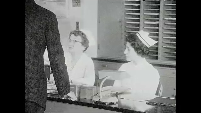 1960s: Women sit at nurses station and talk.  Man approaches desk.  Woman gestures.