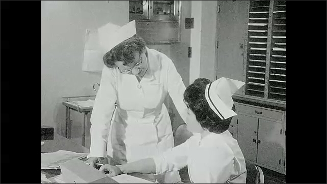 1960s: Nurse stands and discusses paperwork with nurse sitting at desk.