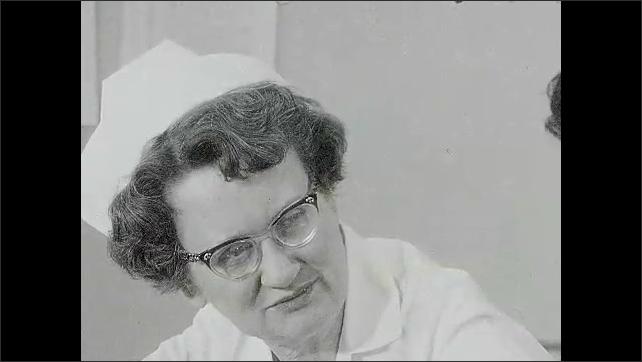 """1960s: Man claps slap that reads """"NURSE 13C."""" Nurse starts talking and sighs. Man claps slate that reads """"NURSE 14A."""""""