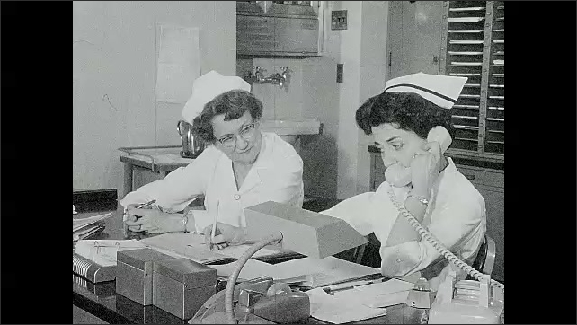 1960s: Nurse talking on telephone. Another nurse listens intently and takes notes.