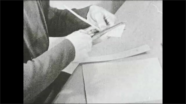 1930s: Woman uses scissors to cut rectangle shapes in paper.