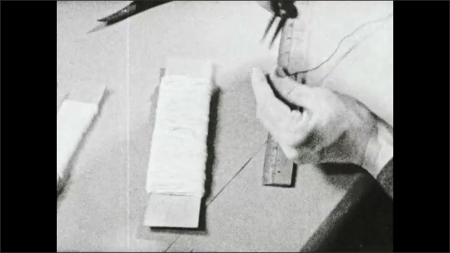 1930s: Title card. Woman sets yarn wrapped piece of cardboard next to ruler, measures wire on ruler and cuts it.