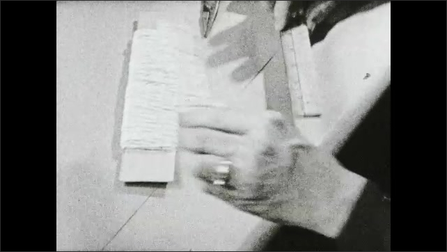 1930s: Woman makes hooks on either end of piece of wire then lays it down next to yarn wrapped piece of cardboard and then measures it with ruler.