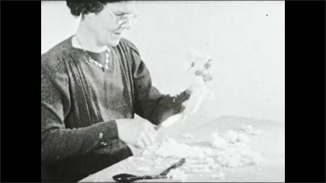 1930s: Woman uses scissors to cut excess pieces of yarn from toy dog made from yarn wrapped piece of cardboard.