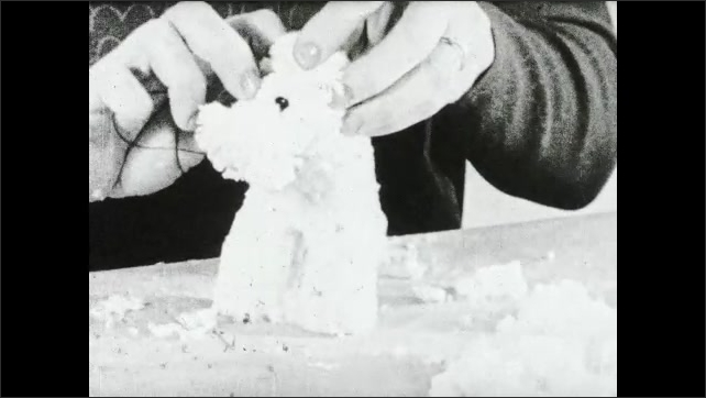 1930s: Woman attaches eyes to toy dog made from yarn wrapped around cardboard.