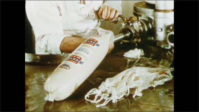 1950s: Man inspects meat hanging from hooks. Man pumps substance into bags.