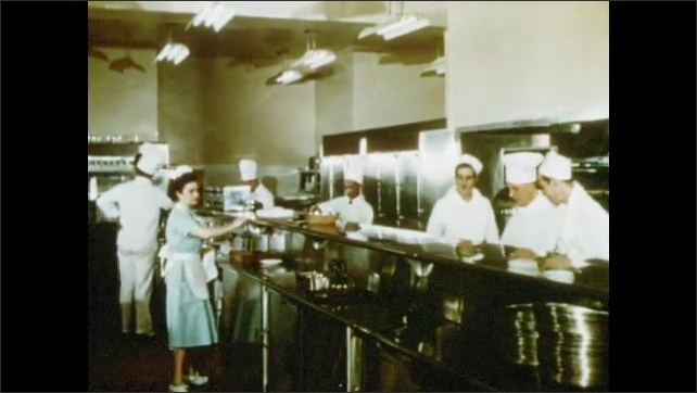 1950s: Workers in commercial kitchen work.