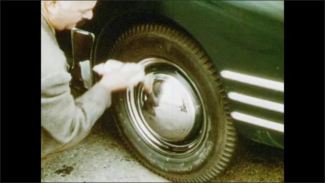 1950s: Man washes hubcap.