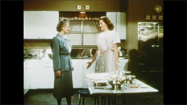 1950s: Women and men enter kitchen. Women speak. Woman gestures at table and picks up pie.