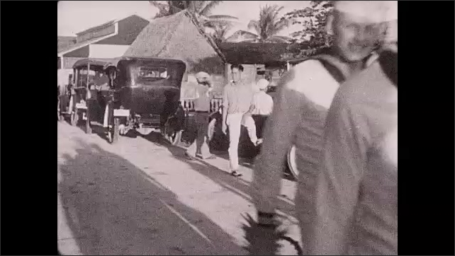 1930s: Philippines: sailors carry bunches of bananas. Sailors holds up Pineapple and fruit