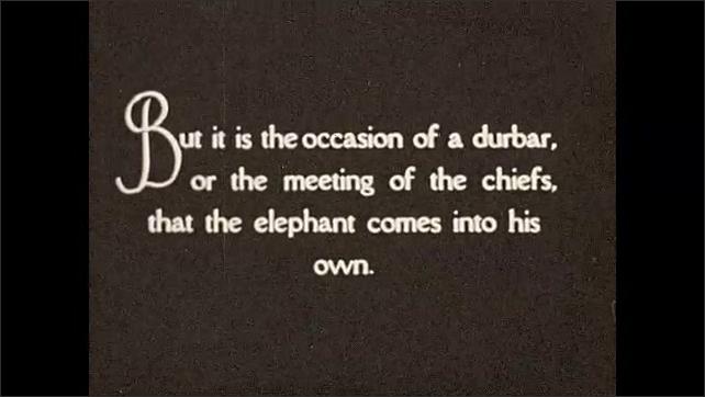 1930s: Intertitle card. Men pose next to elephants. Intertitle card.