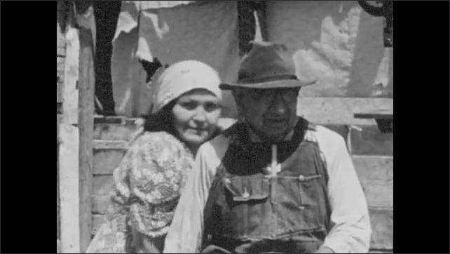 1930s: Paiute home. Family outside a shack with dogs and children. Woman enters wooden cabin.