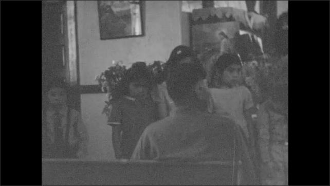 1930s: Lilies and flowers decorate the altar. Children and choir sing at the front of the church as woman plays the piano.