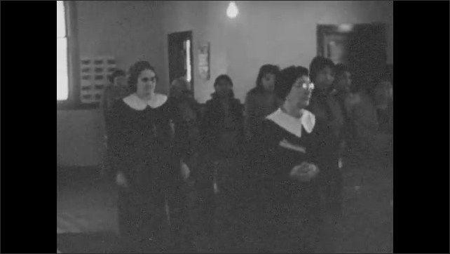 1930s: Choir in robes walks into church. Children walk into church carrying flowers as adults stand in the pews.