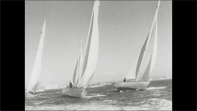 1930s: Text on screen. Ships sail on ocean in regatta. Sailboats race past one another in regatta.