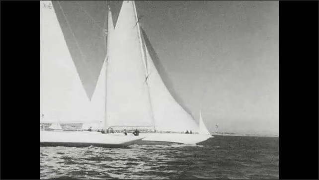 1930s: Men operate sails and steering wheel on sail boat. Sail boats race past one another in regatta. Man pulls rope on sails. Sail boats race on ocean.