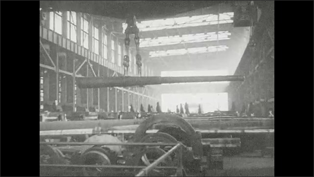 1930s: Smoke trails from blade on metal shaping lathe. Crane moves large artillery cannon across factory floor. Workers scramble in large factory. Crane swings cannon over workers in factory.