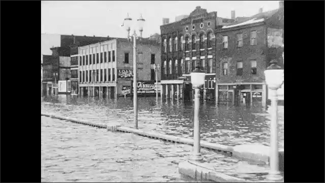 1930s: Intertitle. Water flows, flooded city. People ride a boat in flooded suburbs. Cow tied to house. Intertitle. People, destroyed house. Damaged classroom. Overton Hospital. Nurse checks a child.
