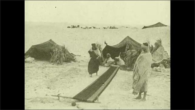 1920s: AFRICA: tribes set up temporary home in desert. Women build tents in desert. Women  work in tents.