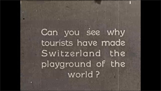 """1920s: Ornate stone building exterior. Outdoor caf?? full of diners. Intertitle """"Can you see why tourists have made Switzerland the playground of the world?"""" House on island in Swiss lake."""