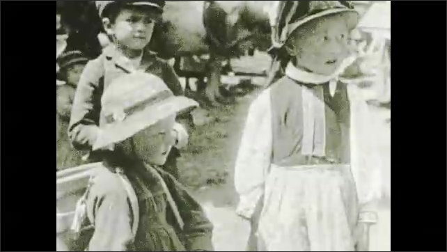 1920s: People walking with cows, woman churning butter in foreground. Close up of kids. People with cow, horse carrying wood. Close up of girl.