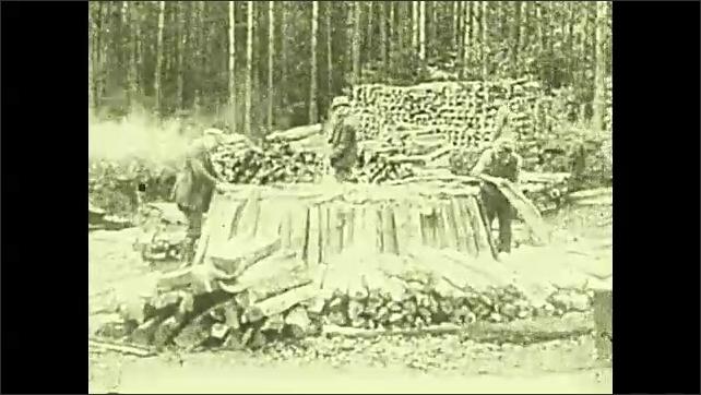 1920s: Intertitle. Men gathering wood into pile. Man walks on smoking wood.