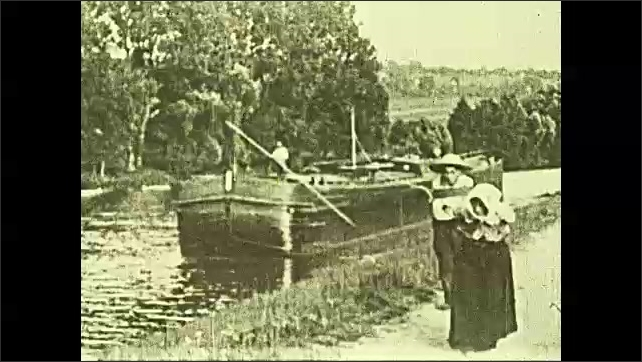 1920s: Boat on river, woman and boy walk toward camera pulling rope tied to boat.