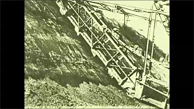 1920s: Pan across mine. Tilt down machine stripping soil from hill. Intertitle. Man drilling into rock.