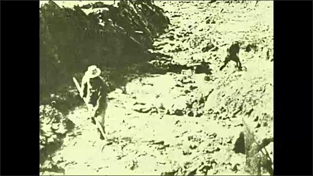 1920s: Mine elevator lowers, iris in. Train dumps coal onto hillside. Man stands in stream with net. Intertitle.