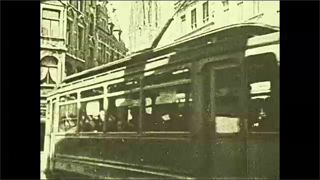 1920s: High angle pan across city center. City street, streetcar passes camera. High angle view of city square with lawns.