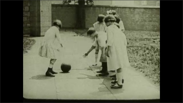 1930s: Little girls bounce ball back and forth.