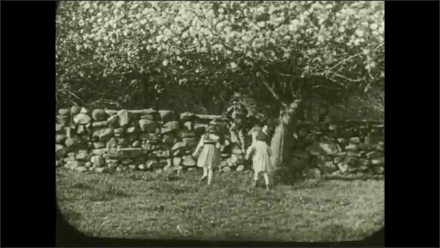 """1930s: Caption reads """"Children have a right to be well born.  The healthiest children are the happiest children.""""  Children run.  Boys walk on stone wall.  Little boy brings girl a flower."""