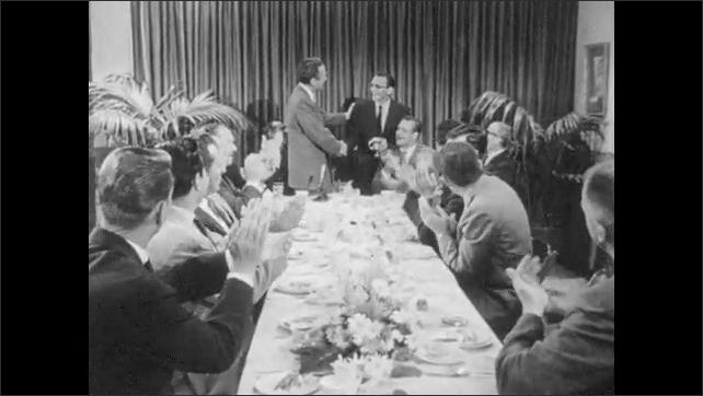 1950s: Banquet.  Man receives award.  Men shake hands.  Men smile and applaud.