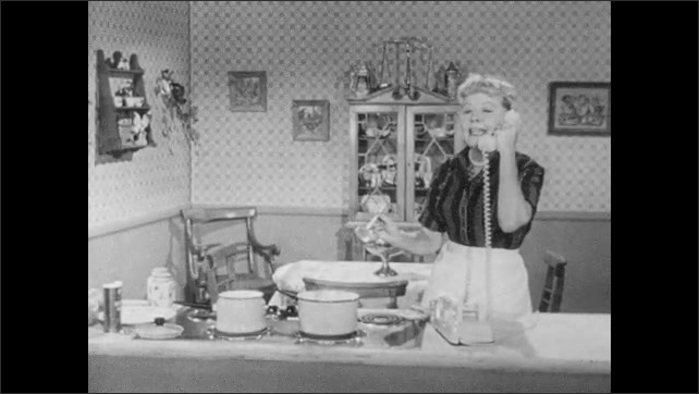 1950s: Kitchen.  Woman talks on the phone.  Woman tastes food.  Woman cooks.
