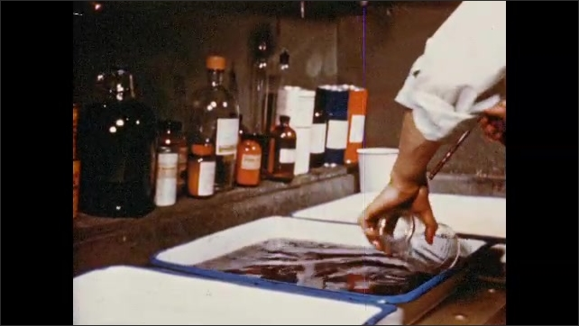1950s: UNITED STATES: jars and bottles by sink. Hand made negatives. Gas burner. Razor sharp knives.